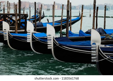 Gondolas lined up on the water, tied to the dock, awaiting tourists on a cloudy grey day in Venice, Italy.
