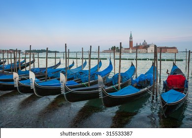 Gondolas moored by Saint Mark square with San Giorgio di Maggiore church in the background - Venice, Venezia, Italy.