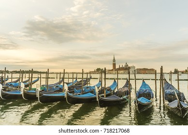 Gondolas moored by Saint Mark square with San Giorgio di Maggiore church in Venice, Italy,