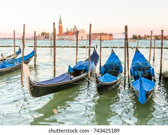 Gondolas moored in the Venetian lagoon. San Giorgio di Maggiore church as background. Venice, Italy