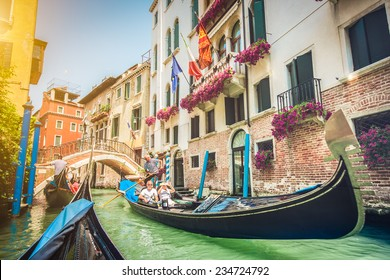 Gondolas on canal in Venice, Italy with retro vintage Instagram style filter and lens flare effect
