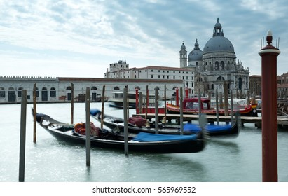 Gondolas on the Grand Canal in Venice with the Santa Mana Della Salute and blue cloudy sky in the background.