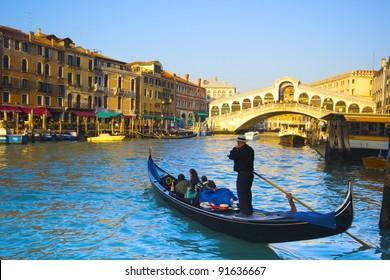 gondolas on the Grand Canal in Venice. Rialto Bridge on background. Sunset
