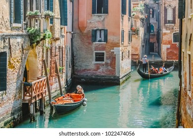 Gondolas on narrow canal and small boat tied next to old red brick house with wooden balcony on narrow canal in Venice, Italy.