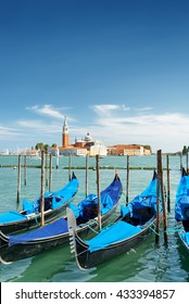 Gondolas parked beside the Riva degli Schiavoni on the Venetian Lagoon in Venice, Italy. The Church of San Giorgio Maggiore on island of the same name is visible in background.
