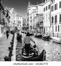Gondolas passing on small canal among old historic houses and bridge in Venice, Italy. Black and white image.