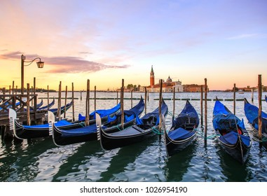 Gondolas at sunrise with view of San Giorgio Maggiore church in the background . Venice, Italy.