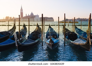 Gondolas at sunrise with view of San Giorgio Maggiore church in the background. Venice, Italy.
