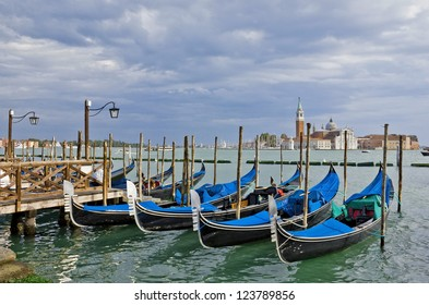 Gondolas waiting for tourists near Piazza San Marco in Venice. View with dramatic sky toward San Giorgio Maggiore.