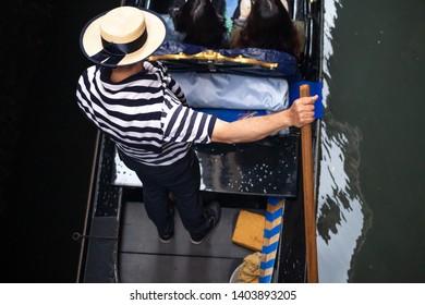 Gondolier carries tourists in gondola, Venice, Italy. Traditional gondolier in Venezia.