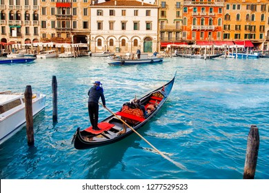 Gondolier carries tourists on gondola Grand Canal of Venice, Italy.