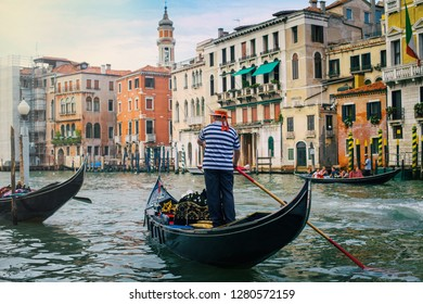 Gondolier dressed in traditional blue striped shirt and straw hat with red ribbon. Venice, Italy.
