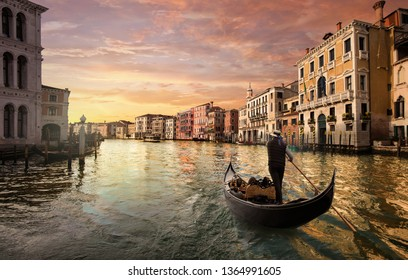 A gondolier is driving his gondola in the grand canal at sunset in Venice, Italy.