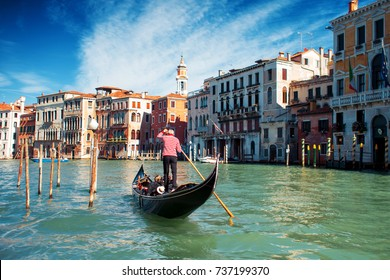 Gondolier floats on the Grand Canal, the Rialto bridge in the background