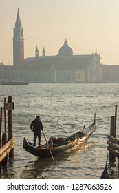Gondolier and gondola entering the Venetian Lagoon on a hazy winter's day with the Church of San Giorgio Maggiore in the background