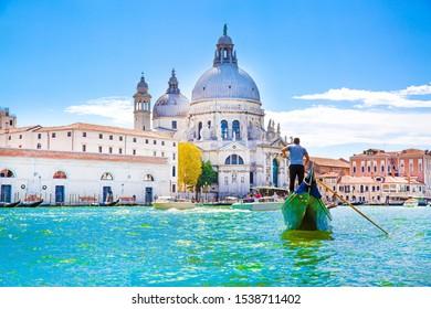 Gondolier and gondola on Grand Canal, Basilica Santa Maria della Salute in Venice, Italy. Sunny summer day with blue sky.