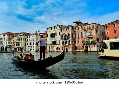A gondolier in a gondola on a Venice canal in Italy. A typical venetian landscape.