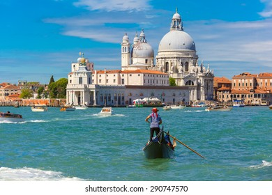 Gondolier in a gondola rides on Canal Grande in a hat with a red ribbon and a typical striped singlet, Basilica di Santa Maria della Salute in the background, Venice, Italy. Selective focus on