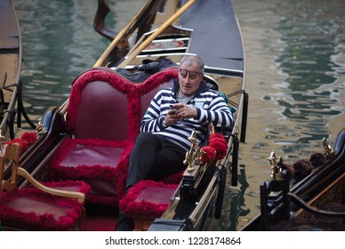 Gondolier with mobile phone in Venice on 04-02-2018 (4498)
