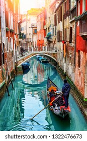 Gondolier on gondola boat in Venice, Italy. Old water canal and colorful architecture in Venice. Venetian landmark in Italy.