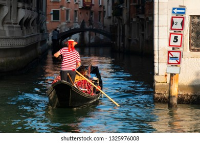 gondolier on a gondola carries tourists along the canal in Venice