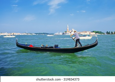 Gondolier on a gondola on the Grand Canal in Venice, Italy. Gondola's are a major mode of touristic transport in Venice