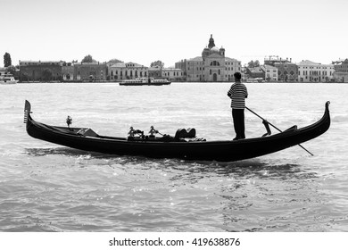 Gondolier on a gondola, Grand Canal in Venice, Italy.