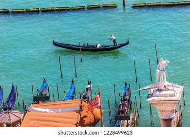 A gondolier is ruling his gondola in a channel of Venice near the pier