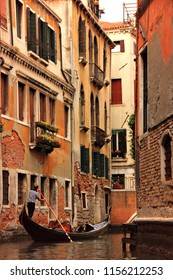 A gondolier steers his gondola through the narrow canals beneath ancient medieval buildings in Venice, Italy.
