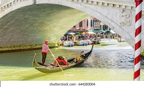 Gondolier under the Rialto Bridge of Venice, Italy