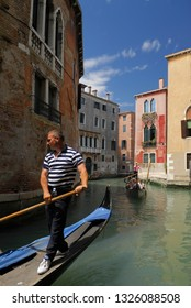 Gondolier whistling to an oblivious colleague on a canal in Venice, Italy - May 23, 2007