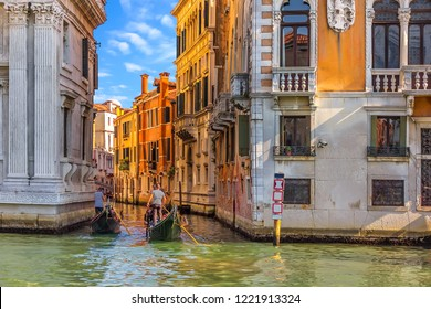 Gondoliers at work in a typical canal of Venice