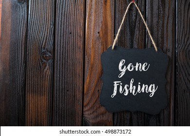 Gone Fishing Sign Written In Chalk On Chalkboard On Rustic Vintage Wood Background. Top View Selective Focus.