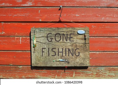 Gone Fishing Sign Written On A Wooden Plaque Hanging On A Weathered Wooden Fence.