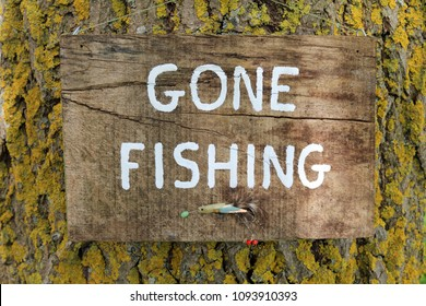 Gone Fishing Sign Written On A Wooden Plaque Hanging On A Tree.