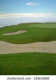 Gone Golfing handwritten in the sand on a golf course with an ocean view