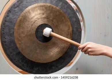 Gong and the hand holding gong beater