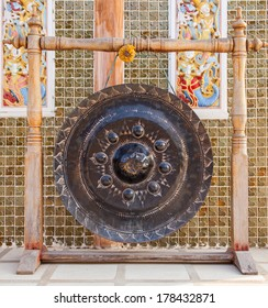 gong hanging on wooden poles in thai temple