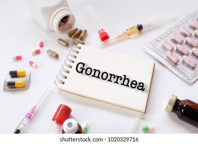Gonorrhea - Diagnosis written on a white piece of paper. Treatment and prevention of disease. Syring and vaccine with drugs. Medical and Healthcare concept. Selective  focus
