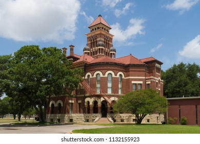 The Gonzales County Courthouse is a red brick three story eclectic Romasnesque Revival structure with white limestone trim