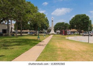 GONZALES, TEXAS - JUNE 10 2018: a town square, a monument and some yellowed grass