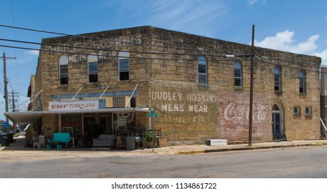 GONZALES, TEXAS - JUNE 10 2018: a hundred year old stone building shows signs of many different commercial ventures