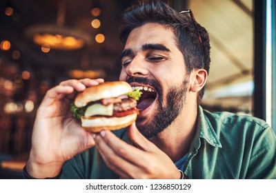 Good appetite. Young man sitting in a cafe and enjoying in breakfast. Food, lifestyle concept
