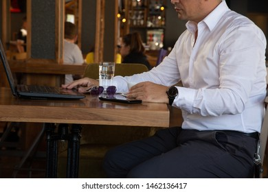 Good attractive man sitting in the chair in restaurant, drinks coffee  working on his lap top, with mobile phone on table. Take his brake in cafe and working simultaneously.
