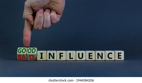 Good or bad influence symbol. Businessman turns cubes and changes words 'bad influence' to 'good influence'. Beautiful grey background. Business, good or bad influence concept. Copy space.