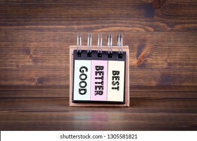 Good, better, best concept. notebook on dark wood background, table