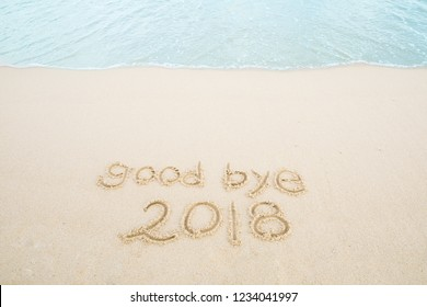 good bye 2018 written on the sand beach.