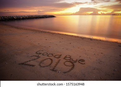 Good Bye 2019 concept. Good Bye 2019 written on the sand at beach with beautiful sunset background.