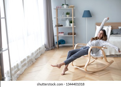 Good day! Happy cute pretty woman lying in the armchair on the weekend and stretching.