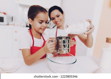 Good Day For Mother and Daughter. Happy Day with Young Girl in Kitchen. Love Mom with Young Girl Percolate Flour for Sweet Biscuit and Cake. Little Girl with Mother in Apron. Kitchen with Food and Pie